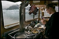 Woman preparing a breakfast aboard small tour boat. Glacier Bay National Park ( color)