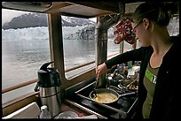 Woman cooking eggs aboard small tour boat, with glacier in view. Glacier Bay National Park, Alaska, USA. (color)