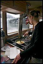 Woman cooking eggs aboard small tour boat, with glacier outside. Glacier Bay National Park ( color)