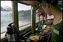 Woman prepares breakfast eggs aboard small tour boat, with glacier in view. Glacier Bay National Park ( color)