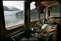 Breakfast potatoes in a small boat moored in front of glacier. Glacier Bay National Park ( color)
