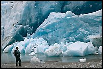 Hiker looking at ice wall at the front of Reid Glacier. Glacier Bay National Park, Alaska, USA. (color)