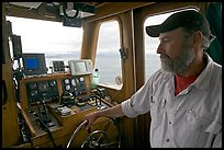 Captain steering boat with navigation instruments. Glacier Bay National Park ( color)