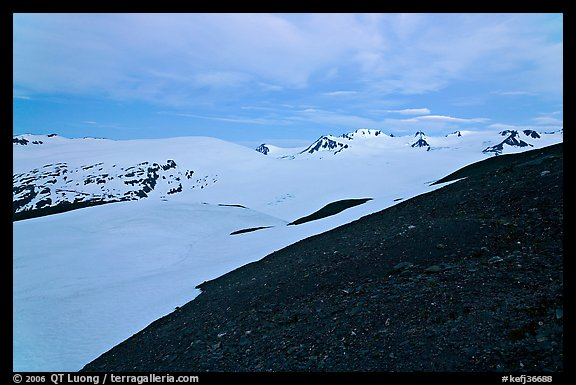 Rocky slope and snow-covered Harding Icefield at dusk. Kenai Fjords National Park, Alaska, USA.