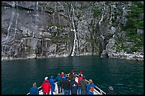 Waterfall viewing from deck of tour boat, Cataract Cove. Kenai Fjords National Park, Alaska, USA.