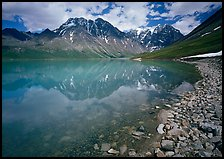 Shore of Turqouise Lake with Telaquana Mountains reflected in silty water. Lake Clark National Park ( color)