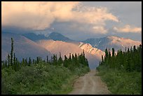 Gravel road leading to mountains lit by sunset light. Wrangell-St Elias National Park ( color)