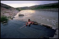 Visitor relaxes in hot springs next to Rio Grande. Big Bend National Park, Texas, USA. (color)