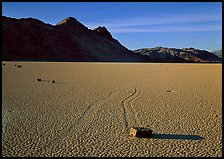 Tracks, moving stone on Racetrack playa and Ubehebe Peak, late afternoon. Death Valley National Park ( color)