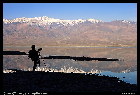 Photographer and Panamint range reflected in a seasonal lake, early morning. Death Valley National Park, California, USA.