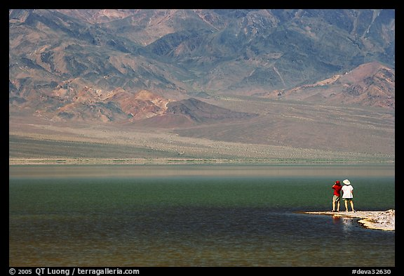 Two tourists on shore of rare lake on the floor of the Valley. Death Valley National Park, California, USA.