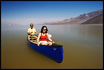 Canoists in rarely formed Manly Lake with Black Mountains in the background. Death Valley National Park ( color)