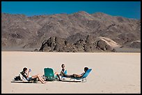 Tourists sunning themselves with beach chairs on the Racetrack. Death Valley National Park ( color)