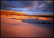 Red light of sunset on white sand dunes and Guadalupe range. Guadalupe Mountains National Park, Texas, USA.