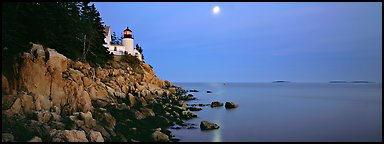 Dusk seascape with lightouse, moon, and reflection. Acadia National Park, Maine, USA.