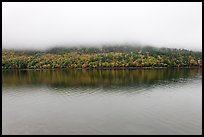 Hill reflected in Jordan Pond with top covered by fog. Acadia National Park, Maine, USA.