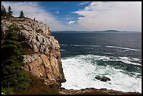 Tall granite sea cliff with person standing on top. Acadia National Park, Maine, USA.