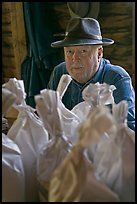 Miller sitting behind bags of cornmeal, North Carolina. Great Smoky Mountains National Park, USA. (color)