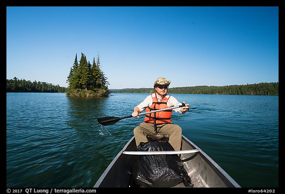 Canoist paddling and islet, Tobin Harbor. Isle Royale National Park (color)