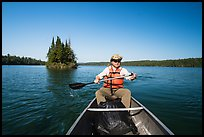 Canoist paddling and islet, Tobin Harbor. Isle Royale National Park ( color)