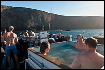 Divers relaxing in hot tub aboard the Spectre and Annacapa Island. Channel Islands National Park, California, USA. (color)