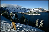 Photographer on  rim of  Lake in winter. Crater Lake National Park, Oregon, USA. (color)