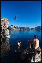 Man jumping from cliff as others look, Cleetwood Cove. Crater Lake National Park ( color)