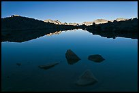 Rocks and calm lake with reflections, early morning, Dusy Basin. Kings Canyon National Park, California, USA.