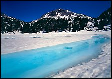 Turquoise melting snow in lake Helen and Lassen Peak, late spring. Lassen Volcanic National Park, California, USA. (color)