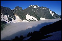 Sun projected on fog below peaks, early morning, Cascade Pass area, North Cascades National Park. Washington, USA.