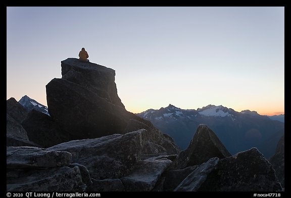 Man sitting on rock contemplates mountains at sunrise, North Cascades National Park.  (color)