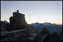 Man sitting on rock contemplates mountains at sunrise, North Cascades National Park.  ( color)