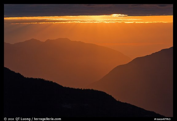 Layered ridges with sun behind clouds, North Cascades National Park.  (color)