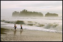Children running along surf, Rialto Beach. Olympic National Park, Washington, USA.