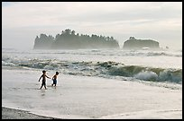 Children playing in water in front of sea stacks, Rialto Beach. Olympic National Park, Washington, USA.