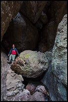 Man with headlamp looking up in Balconies Cave. Pinnacles National Park, California, USA. (color)