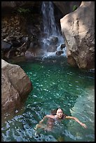 Girl swims in cool pool at the base of Wapama falls. Yosemite National Park, California, USA. (color)