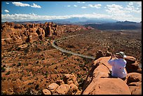 Tourist taking picture from top of fin. Arches National Park, Utah, USA. (color)