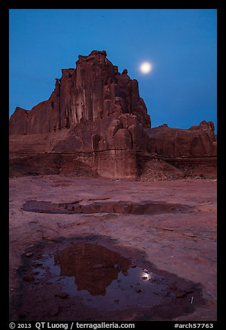 Courthouse tower and moon at night. Arches National Park, Utah, USA.