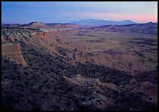 Cliffs, basin, and snowy mountains at dusk, Upper Desert, dusk. Capitol Reef National Park, Utah, USA.