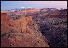 Waterpocket Fold and snowy mountains at dusk. Capitol Reef National Park, Utah, USA.