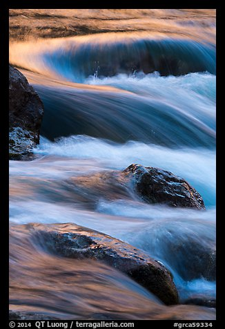 Boulders and rapids with warm light from canyon walls reflected. Grand Canyon National Park (color)