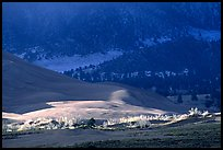 Storm light illuminates portions of the dune field. Great Sand Dunes National Park and Preserve, Colorado, USA.