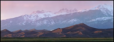 Sand dunes below snowy mountain range at sunset. Great Sand Dunes National Park (Panoramic color)