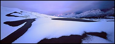 Snow-covered dune landscape and mountains at dawn. Great Sand Dunes National Park (Panoramic color)