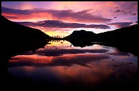 Colorful sunrise clouds reflected in a pond in Horseshoe park. Rocky Mountain National Park, Colorado, USA. (color)