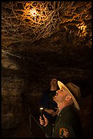 Ranger pointing flashlight at boxwork. Wind Cave National Park, South Dakota, USA. (color)