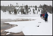 Cross country skiers pass Chromatic Spring. Yellowstone National Park, Wyoming, USA. (color)
