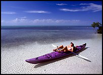 Woman reclining in kayak on shallow waters,  Elliott Key. Biscayne National Park, Florida, USA. (color)