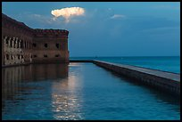 Moat, fort, bright cloud at dawn. Dry Tortugas National Park, Florida, USA. (color)